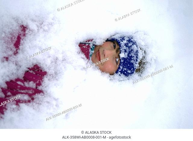Child buried in snow Russian Jack Park Anchorage SC AK winter portrait