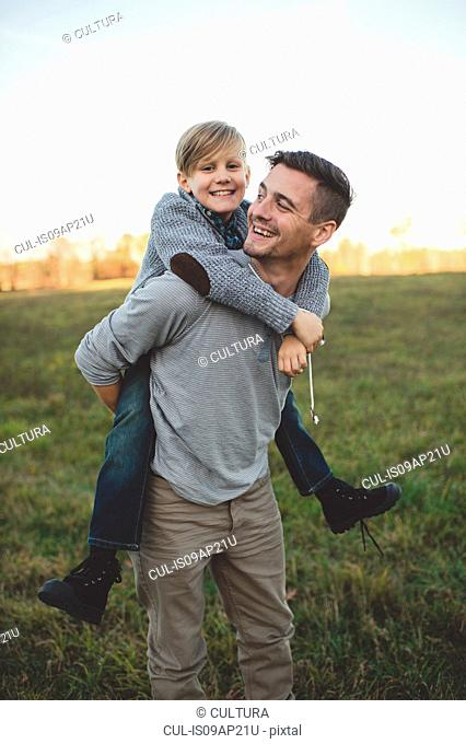 Boy getting piggy back from father in field