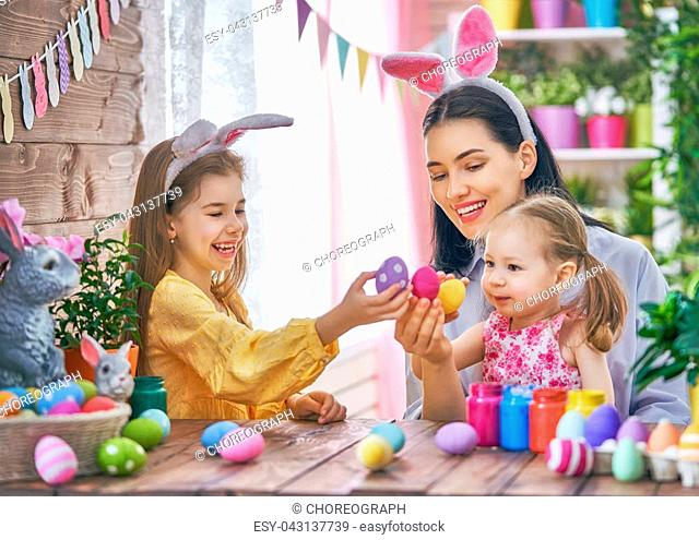 Happy holiday! A mother and her daughters are painting eggs. Family preparing for Easter. Cute little children girls are wearing bunny ears