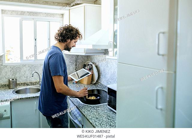 Man cooking in kitchen while looking at tablet