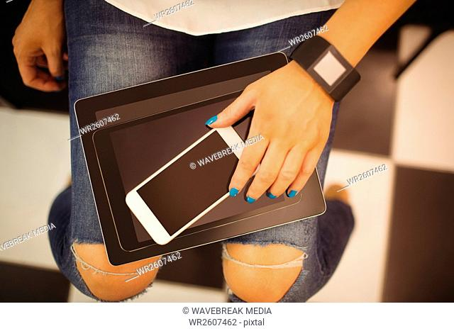 Hand of woman holding mobile and digital tablet