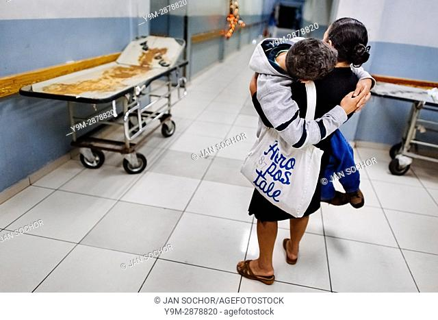 A Salvadoran woman carries his ill son while seeking an urgent medical help in the emergency department of a public hospital in San Salvador, El Salvador