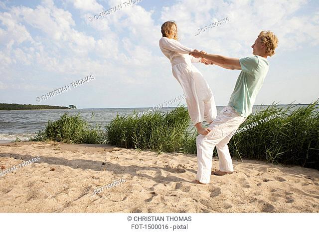 Friend balancing on man's knee at beach against sky