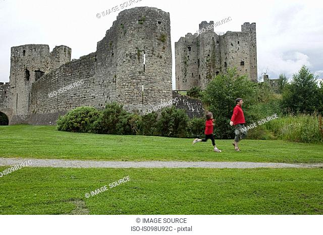 Father and daughter running at Trim Castle, County Meath, Ireland