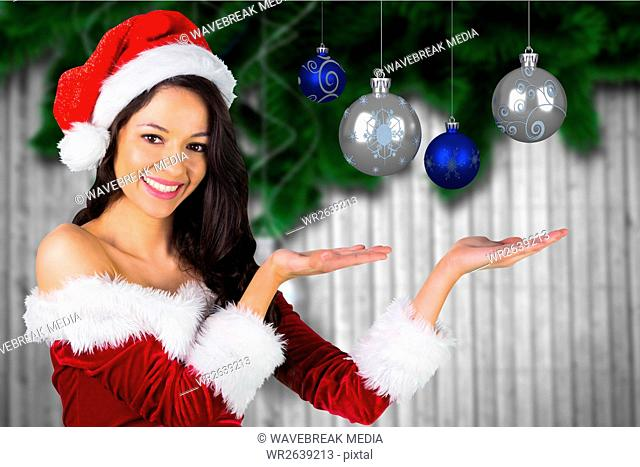 Beautiful woman in santa costume showing christmas baubles