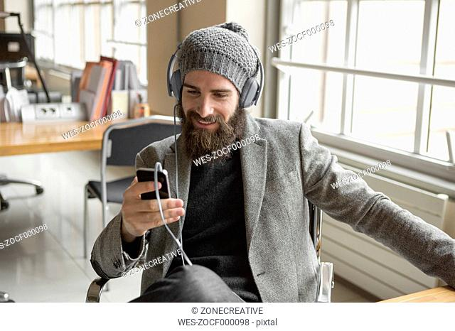 Portrait of young businessman wearing beany hat using smart phone