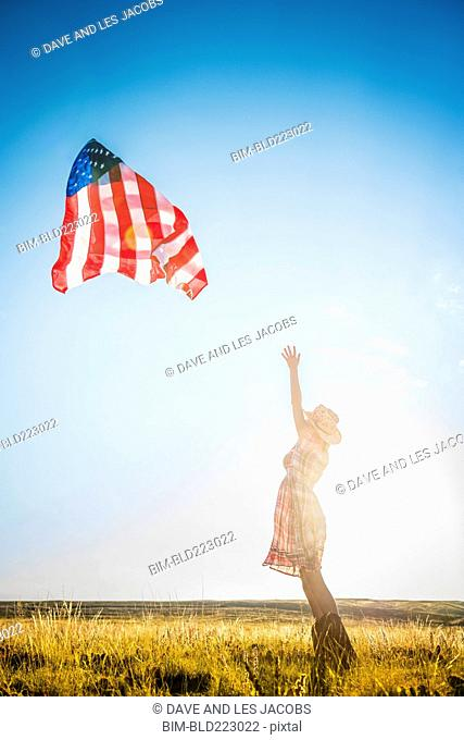 Hispanic woman wearing cowboy hat throwing American flag in desert