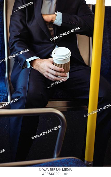 Businessman with disposable coffee cup checking his blazers pocket while travelling