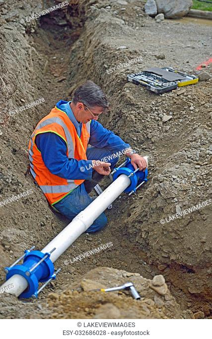 Plumber tightens the joiners on pipes for a broken stormwater drainage system