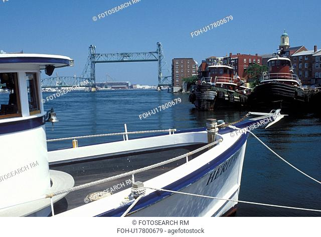 Portsmouth, NH, New Hampshire, Tugboats docked along the Piscataqua River in Portsmouth. View of Memorial Bridge crossing the Piscataqua River