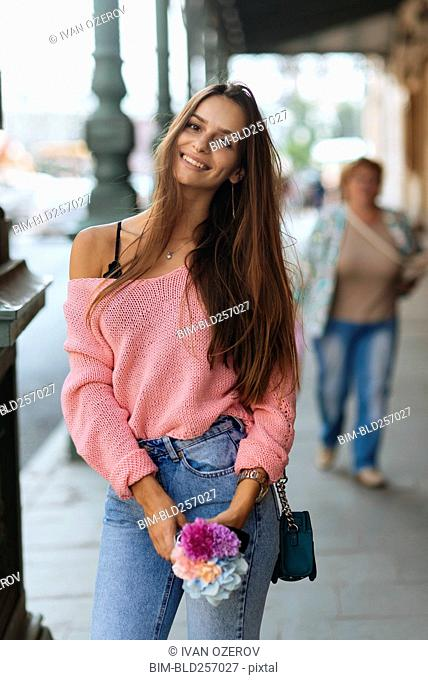 Portrait of Caucasian woman holding flowers on sidewalk