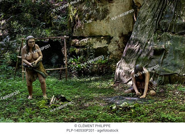 Replica of Neanderthal women working at open air dwelling with shelter made of animal hides from the Magdalenian period at Prehisto Parc