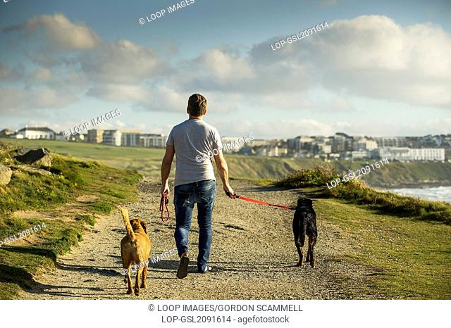A dog walker and his two dogs walk along The Headland in Newquay in Cornwall