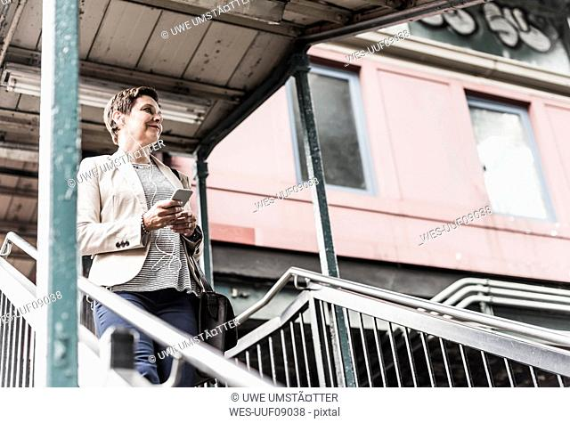 Mature woman using smart phone at commuter train station