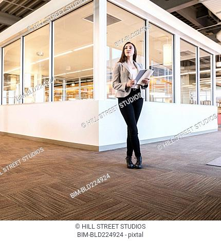 Businesswoman holding notebook in office