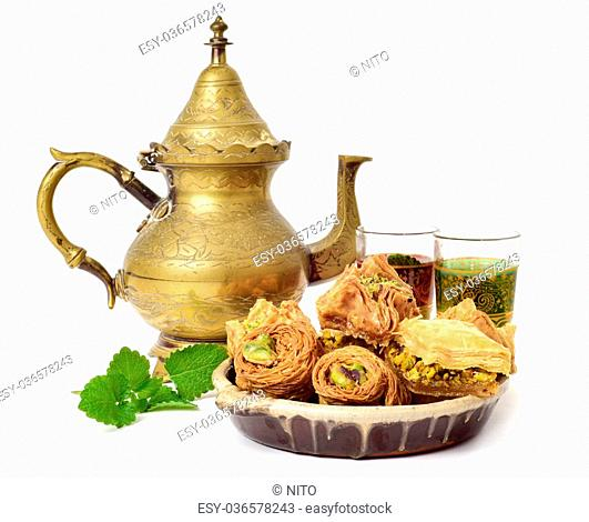 an assortment of different baklava pastries in an earthenware bowl, a golden teapot and some ornamented glasses with tea, on a white background