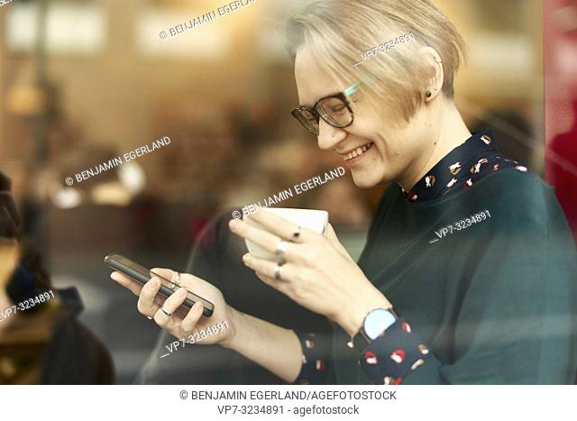 woman behind glass window drinking coffee indoors in café and using smartphone, wearing glasses, happy laughing, in Munich, Germany