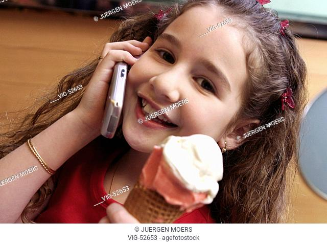 Little girl with icecream making a phone call with a mobile phone (posed). - GERMANY, 18/02/2004