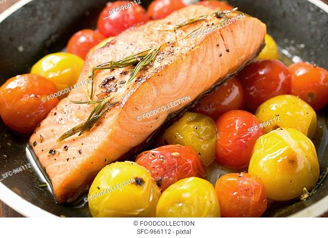 Fried salmon fillet and cherry tomatoes in frying pan