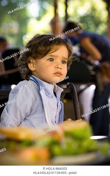 Close-up of a baby boy sitting at a table in a restaurant