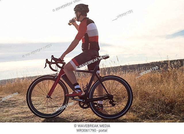 Mountain biker drinking water on countryside