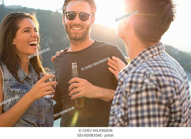 Three adult friends laughing and partying on roof terrace