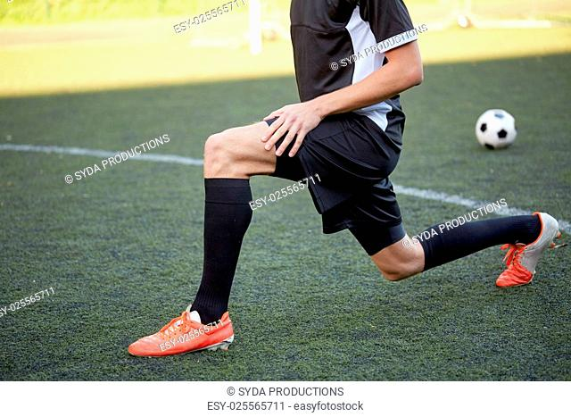 sport, football training and people - soccer player stretching leg on field
