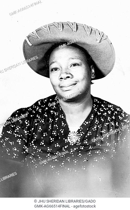 Half length portrait of smiling mature African American woman, wearing a hat and a patterned garment, 1915