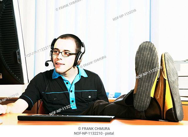 MAN IN OFFICE WITH HIS FEET ON THE DESK