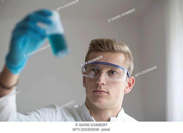 Young scientist analysing test tube in Laboratory, Freiburg im Breisgau, Baden-Württemberg, Germany