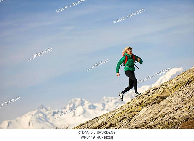 A jogger running over rocky mountains