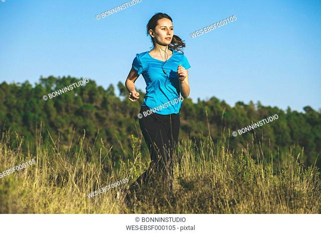 Young female jogger on the move in front of forest