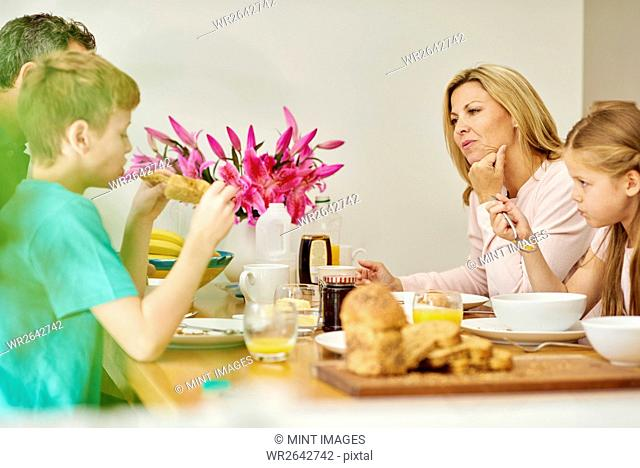 A family of four people, parents and two children eating breakfast