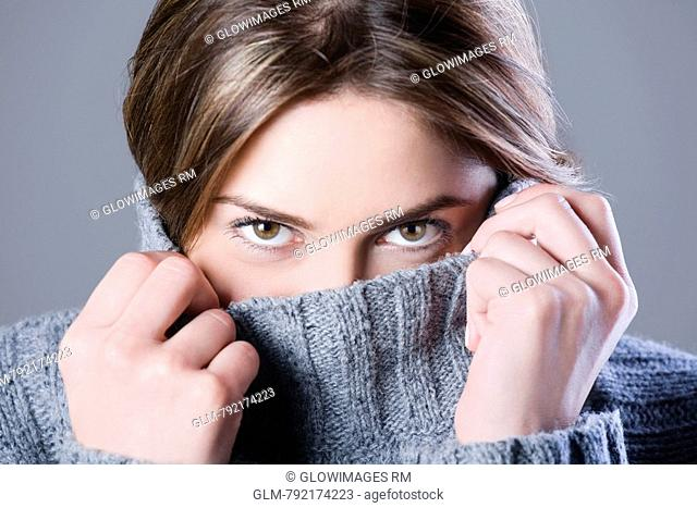 Portrait of a young woman hiding her face with turtleneck collar