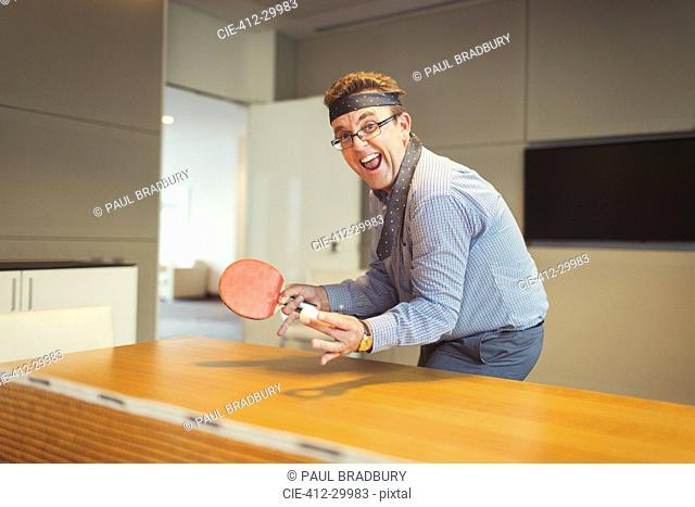 Portrait of enthusiastic businessman playing ping pong with tie wrapped around head in conference room