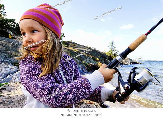 Girl holding fishing rod beside sea