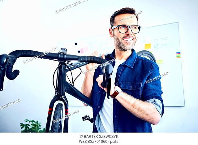 Smiling businessman carrying bicycle in office