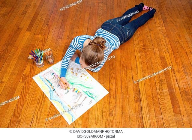 Girl lying on floor drawing picture