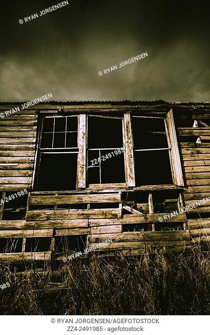 Shattered windows and blown away boards lay to waste a dilapidated rural house in storms of disrepair. Blown away