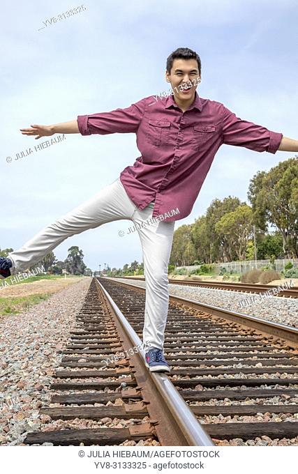 Young man balancing on railway traclks in Calsbad, California