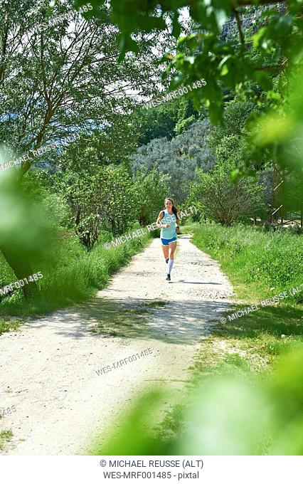 Italy, Trentino, woman running near Lake Garda