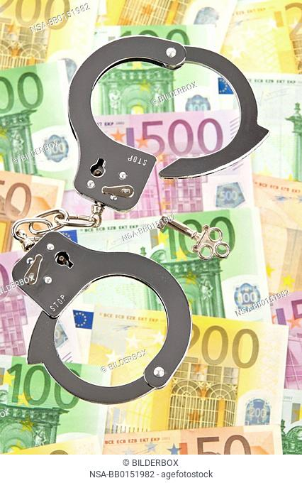 Many Euro bank notes with handcuffs