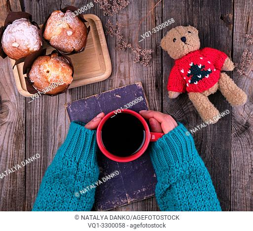 women's hands in a green knitted sweater holding a red ceramic mug with black coffee, gray wooden table