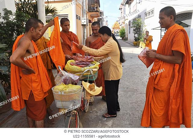Phnom Penh (Cambodia): some monks buying orange T-shirts from a seller arrived at the temple by bicycle