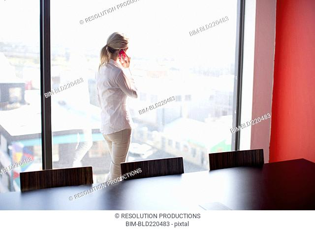 Caucasian businesswoman talking on cell phone in conference room