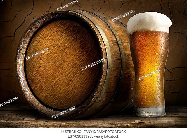 Beer in cask and glass on wooden table