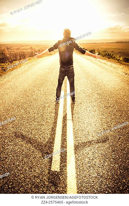Man feeling unstoppable while standing on a highway with hand held high. Joy of living in the moment
