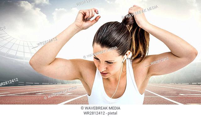 Female runner tying up hair on track against flares