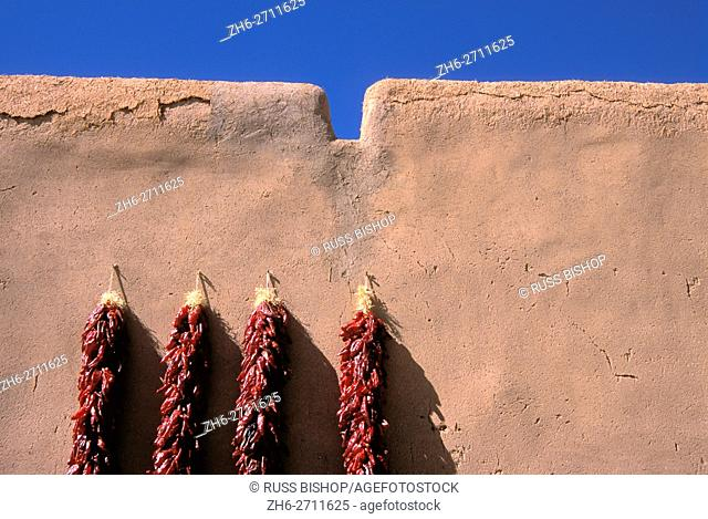 Large chili ristras on adobe wall at the entrance to the Martinez Hacienda (circa 1804), Taos, New Mexico USA