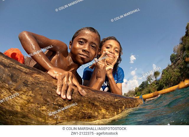 Boy and girl on canoe at Pura Island near Alor in eastern Indonesia